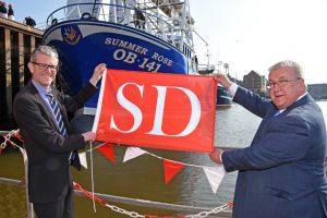 David Burke presents a Sunderland Marine flag to John McAlister at the scalloper's naming ceremony.
