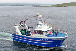 Tranquility approaches Whalsay for the first time, with flags flying proudly after family and friends boarded the fly-shooter at Lerwick. (Photo: Ivan Reid)