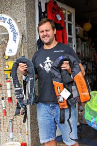 Neal Turner showing just two of the makes of lifejacket on sale at Newline Chandlery – right is the Challenger and left is the Kru.