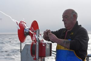 Skipper Andrew Buchan rigging a new trace of hooks on the…