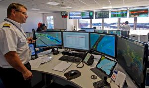 Watch manager Martin Thomas in the Vessel Traffic Services operations room, leading his team of Matthew Dann (left) and Raymund Abosejo, watching movements through the binoculars.