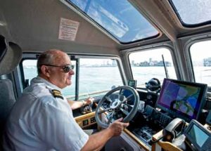 Coxswain marine officer Paul Tomlinson at the helm of Hampstead, a Halmatic Nelson 48/50 boat, watching the radar screens displaying the busy shipping traffic in the Solent.