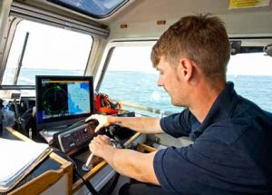 Second coxswain Max Dillingham checking the positions of shipping on the split-screen radar and plotting displays en route to a call-out.