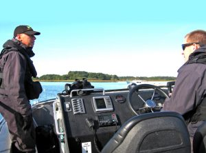 Fishery officers Sam Dell and David Mayne onboard SIFCA's patrol vessel in Poole Harbour.