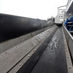 The catch conveyors deliver the contents of the dredges forward into an enclosed area…