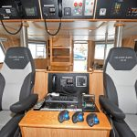 Two NorSap seats flank an island console in the wheelhouse.