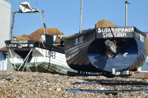 Nick Jenkins' two boats, Challenger and Susan Amanda, together on the Lancing shingle beach, beside his lockers and winch cables.