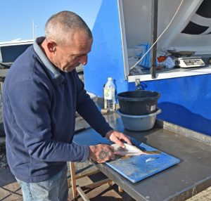 "Nick Jenkins prepares fish for one of his regular customers. ""Supplying fresh fish from the sea is what our business is all about."""