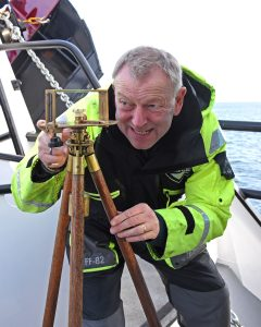Thomas Gunn of Poseidon Navigation Services Ltd lines up marks along the Moray coast while adjusting the compass on Westro.