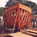 Starting to plank the fully-framed hull of Tudor Rose in the Greensleeves boatyard at Poole in 1988.