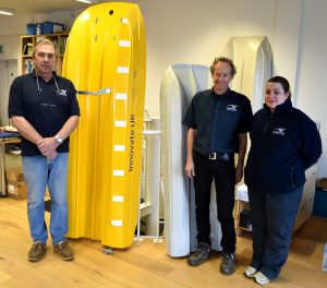 Left to right: general manager Barry Sales, managing director Sean Strevens and office manager Zoe Wilmot Aimes in front of tank testing models of the 9.95m and the new 12m catamaran hulls.