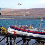The preserved lifeboat Thomas McCunn on the slipway outside the old lifeboat house, with the Coastguard helicopter.