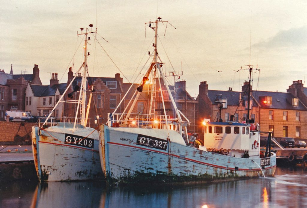 The Danish-built Grimsby pair-trawlers Tino GY 203 and Samantha GY 327 berthed in the south harbour, while their crews repair torn gear on the quay.