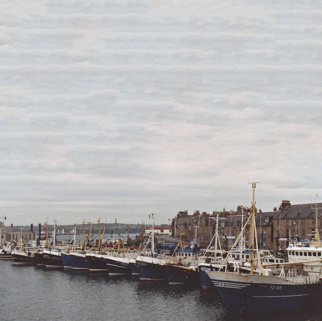Fourteen boats lying stern-to in the south harbour, with the old lifeboat house visible in the background.