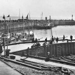 The North Pier packed with visitors waiting to go to sea on cobles and a paddle steamer.