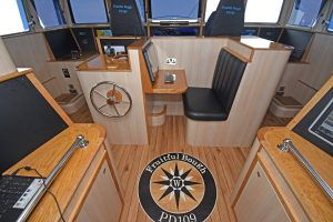 A customised compass rose is incorporated into the wheelhouse floor, between the trawl console and the central desk area.