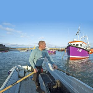 Skipper Luke Noakes rows the skiff away from the quay across to Valentine.