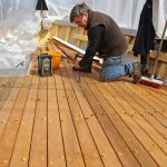 Bobby Cann at work on the new opepe hardwood-planked deck now in place on the Dartmouth crabber Superb-Us.
