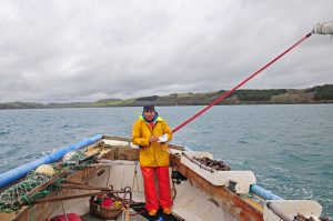 Chris Vinnicombe enjoys a well-earned sandwich as he sails Rachael Anne back upwind to start another drift.