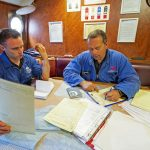 Roger Gee and Charles Blyth write up their findings on the inspection report form after completing the vessel survey.