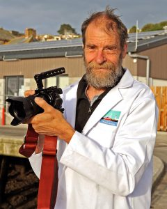Larry Hartwell at Newlyn, capturing events – he has his own small workspace in a fisherman's storage unit, a kettle, and his uniform for the market.
