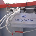 A KIM MOB safety ladder is secured to the gunwale rail aft.