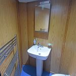 A shower/WC compartment is positioned in the forward port corner of the deckhouse.