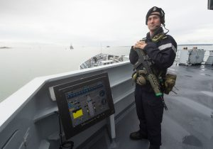 AB (Sea) Lee Bolton providing force protection on HMS Tyne as she leaves Portsmouth.