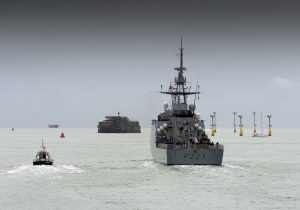HMS Medway being escorted by a Royal Navy pilot boat through the Solent deepwater channel.