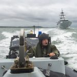 AB (Sea) Iain Barrowman at the helm of a Pacific 24 RIB, with HMS Tyne astern.