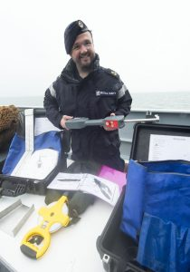 LET (CIS) Harry Perks holding the Omega mesh gauge that is used for checking fishing nets.