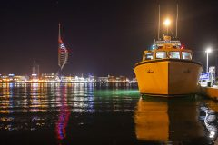 Ted Legg refuelling Jenny G, with the Portsmouth Spinnaker in the background.