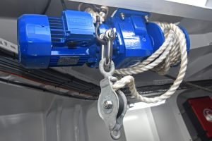 An electric-drive winch mounted on the underside of the shelterdeck is used to pull stacks of boxes toward the fishroom hatch when landing.