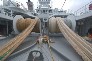 Pulling two SNG midwater trawls onto the net drums, which are arranged side by side on the shelterdeck.