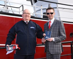 Peterhead Fishermen's Mission superintendent Steve Murray presents a copy of the New Testament to skipper James West during the naming ceremony of the new twin-rig trawler Westro.