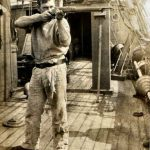 A crewman aboard minesweeper HMS Collena fires a rifle to try to detonate an unexploded mine.
