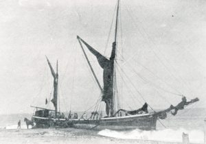 The sailing barge Service ashore at Eccles, just up from Palling, in 1906. The Palling men are offloading coal into carts before attempting to refloat her.