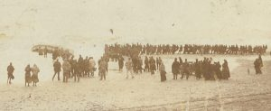 Onlookers watch as the grounded Caister lifeboat Beauchamp is hauled ashore in 1901. Capsized in the surf, it lost nine of its crew.