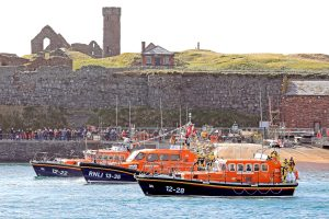 The new Peel 13m Shannon lifeboat Frank and Brenda Winter, flanked by the station's former and temporary boats Ruby Clery and Mary Margaret, under Peel Castle.