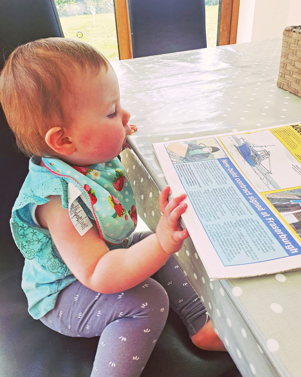 One-year-old Eva Gallagher from Killybegs, Co Donegal, catching up on Fishing News. (Ailbhe Kennedy)