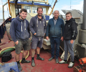 The Brewster family aboard Ruby Doo for a brew-up while waiting for the tide to come back. Wayne, skipper of Ruby Doo (second left), with his son Owen, skipper of Tracey Elaine (left), father Roy and nephew Liam.