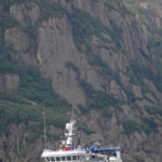 Fjords tower over Harvester as the pair-seiner approaches Flekkefjord early on Sunday morning.