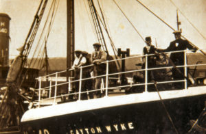 The crew of the Cayton Wyke on the whaleback as the trawler leaves St Andrew's dock.