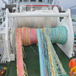 The colour-coded wings of the midwater trawl come off the drum.