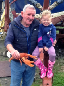 2)Willie MacDonald and his granddaughter hand over the mature orange lobster for release in the same area as the juvenile specimen was returned to the sea.